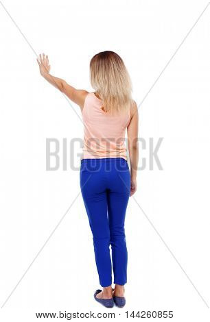 Back view of beautiful woman welcomes. Young teenager girl in jeans hand waving from. Isolated over white background. Blonde in blue pants presses his hand on the button.