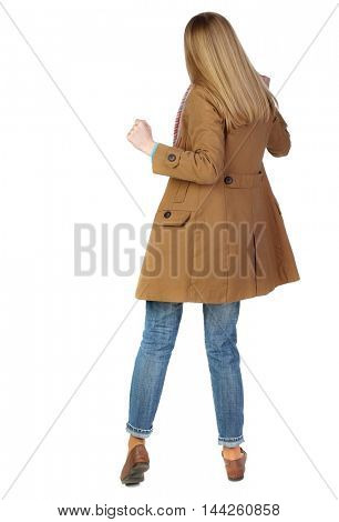 Back view of woman. Raised his fist up in victory sign. blonde in a brown cloak dancing.