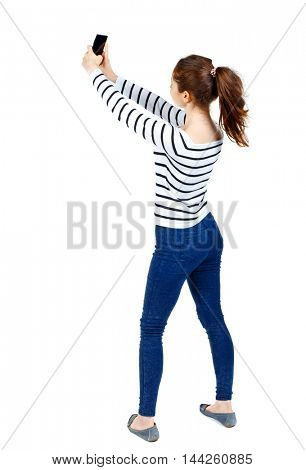 back view of standing young beautiful woman using a mobile phone. girl watching. Girl in a striped sweater photographs that the phone in the sky.