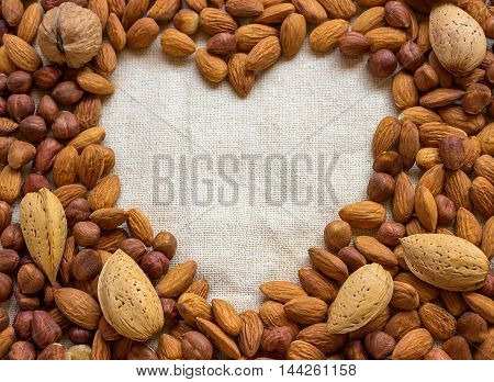 Symbol - the heart. Around a variety of nuts - walnuts almonds hazelnuts. Concept - healthy food.