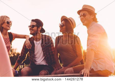Road trip with best friends. Group of young cheerful people enjoying their road trip while sitting in pick-up truck together