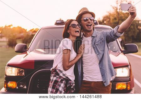 Capturing fun. Beautiful young couple bonding to each other and leaning at their pick-up truck while making selfie