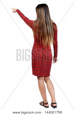 Back view of pointing woman. girl in red plaid dress shows an index finger upwards.