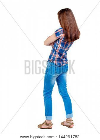 back view of standing young beautiful woman. Girl in plaid shirt standing sideways with his arms folded.