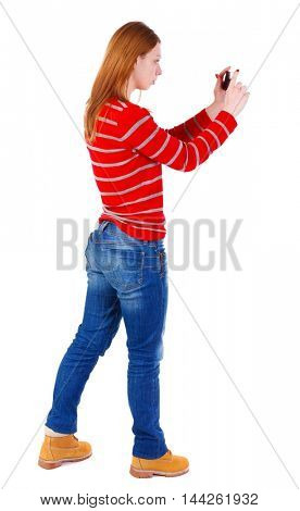 back view of standing young beautiful woman using a mobile phone. The blonde in a red striped sweater photographing something left compact camera.