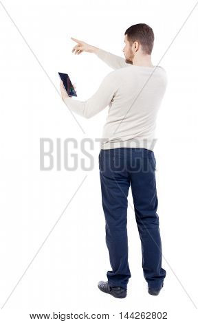 Back view of pointing young men talking on cell phone. backside view of person. Isolated over white background.The bearded man in a white warm sweater reads instructions from the tablet.