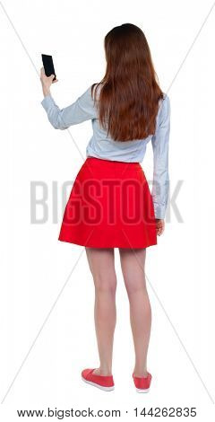 back view of standing young beautiful woman using a mobile phone. girl watching. Long-haired brunette in red skirt is reading from the phone screen.