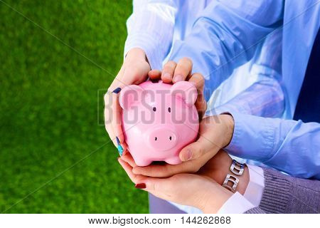 Businessman holding piggy box , standing in office .