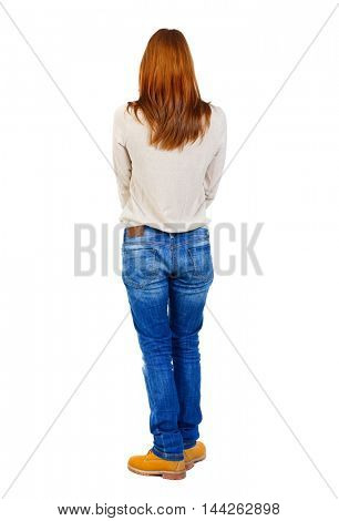 Girl carries a heavy pile of books. back view. Blonde in brown shoes standing back.