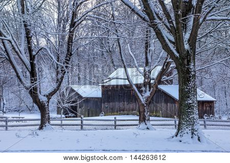 Snow covered trees and an old barn during winter Southwestern Ohio USA