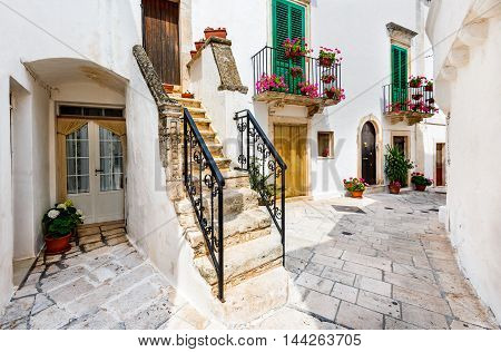 Locorotondo Italy. Medieval whitewashed street and houses in small city of Puglia Apulia Bari region.