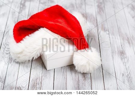 Santa Claus hat over gift box on the wooden background. Winter holidays concept.