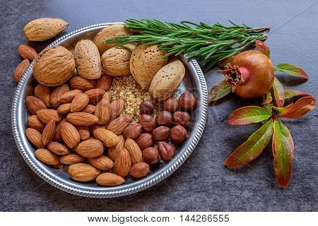 Plate with a variety of nuts. Sprigs of rosemary and pomegranate. Still life. Concept - healthy food.