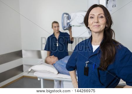 Mature Doctor Smiling While Colleague Taking Patient's Xray