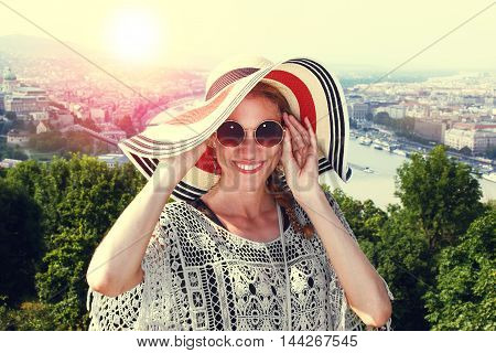 Happy young tourist woman holding glasses in sunset sightsee