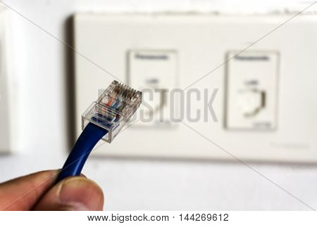 LAN Cable plug to wall outlet for computer netwotk.