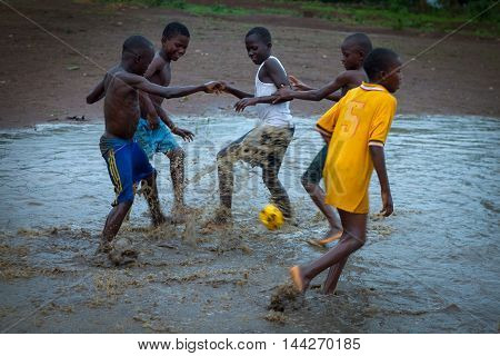Yongoro Sierra Leone - June 02 2013: West Africa the village of Yongoro in front of Freetown children playing football during a rain storm
