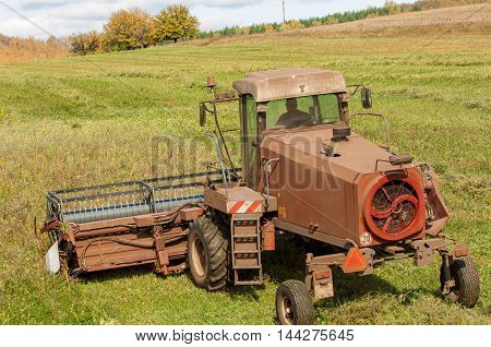 Autumn meadow for mowing grass. harvester for mowing grass. Agricultural image of a large mechanized Swather mowing a grass field to make quality grass hay bales for livestock feed