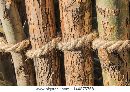 Rope tied in a knot around wooden poles, fence posts. Closeup.