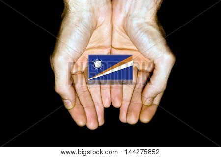 Flag Of Marshall Islands In Hands On Black Background
