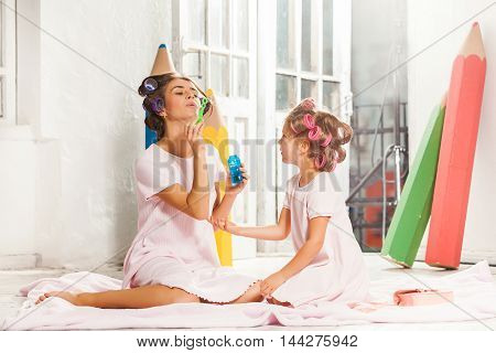 Little smiling girl playing with bubble and her mother on white