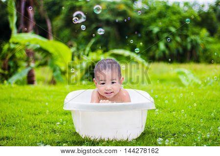 cute baby boy taking water procedures in summer garden
