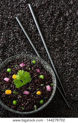 Black rice in a bowl and vegetables
