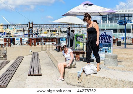 CAPE TOWN, SOUTH AFRICA - FEB 22, 2013: Unidentified tourists in the harbor in Cape Town, South Africa. Cape town is the most popular international touristic destination in Africa