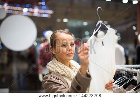 Young woman shopping in a fashion store (color toned image; shallow DOF)