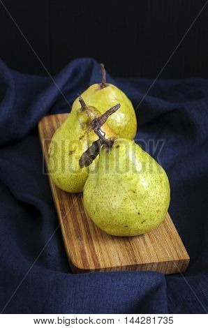 Still Life With Pears On Wooden Desk Against Deep Blue Table Cloth