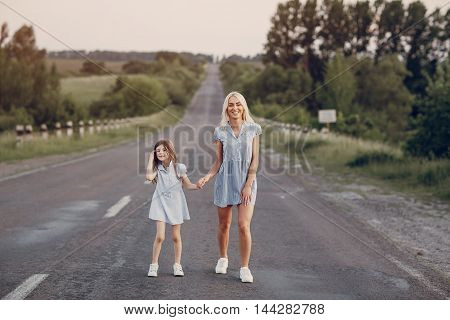 mother and daughter walking together in a field in Sunny summer weather
