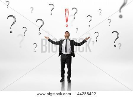 Businessman stands with raised hands looking upwards at an exclamation mark surrounded by question marks isolated on white background. Thinking process. New idea. Solving problems.