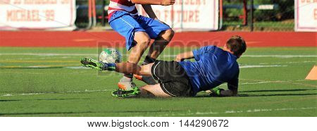 soccer player slide tackles his opponent on a turf field
