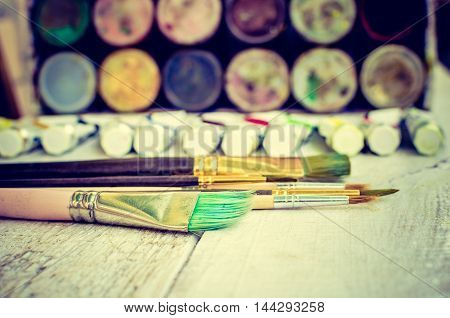 Artist paint brushes oil paint tubes and gouache paint jars on white wooden background.