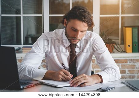 Handsome Young Businessman Sitting At His Workplace Writing A Note. Business Theme