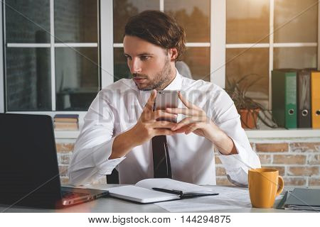 Handsome Young Businessman Sitting At His Workplace Take His Smartphone And Look At The Laptop. Business Theme