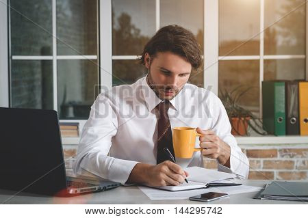 Handsome Young Businessman Sitting At His Workplace Writing A Note And Drinking Tea. Business Theme