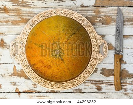 ripe melon on a golden platter and a knife on an old white table top view close-up