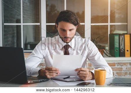 Handsome Young Businessman Sitting At His Workplace And Looking At Paper. Business Theme