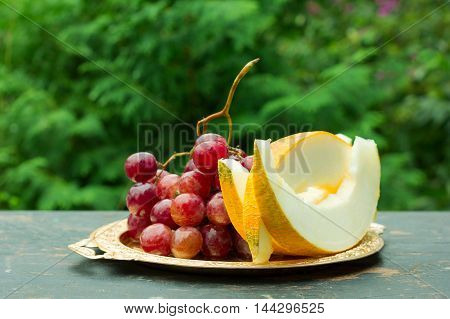 cut slices of ripe yellow melon and a bunch of grapes on a table with natural green background. shallow depth of field