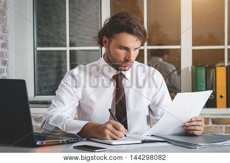 Handsome Young Businessman Sitting At His Workplace Writing A Note And Looking At Paper. Business Theme