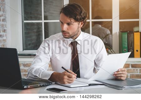 Handsome Young Businessman Sitting At His Workplace Writing A Note And Looking At His Notebook. Business Theme