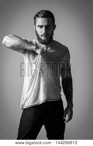 Handsome Bearded Man With Tattoo In Grey T-shirt Posing On Background. Model Tests