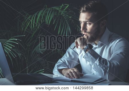 Handsome Young Bearded Businessman Sitting At His Workplace Looking At His Laptop. Business Theme