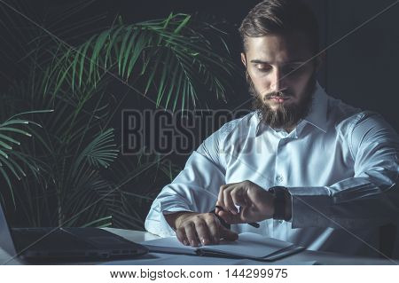 Handsome Young Bearded Businessman Sitting At His Workplace And Looking At His Watch. Business Theme