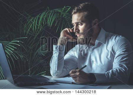 Handsome Young Bearded Businessman Sitting At His Workplace Writing A Note And Talking At Smartphone. Business Theme