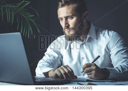 Handsome Young Bearded Businessman Sitting At His Workplace Writing A Note. Business Theme