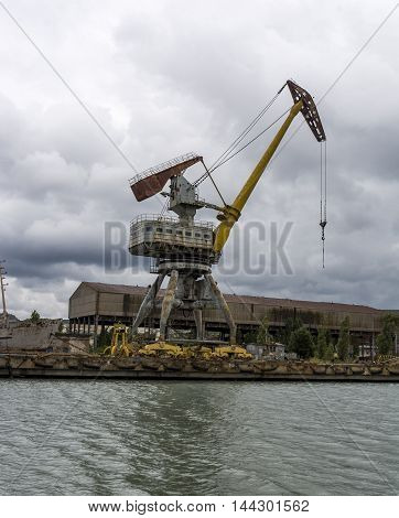 Rusty port crane in a cargo port. Stock photo