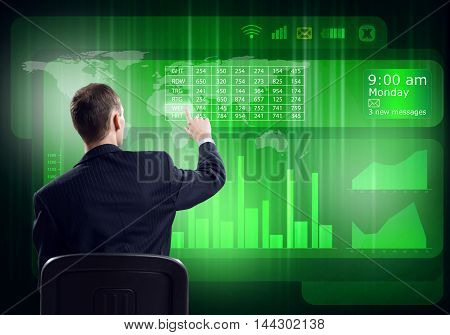 Young businessman sitting on chair and working with virtual panel