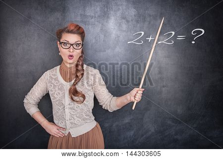 Surprised Teacher With Pointer On Chalkboard Background